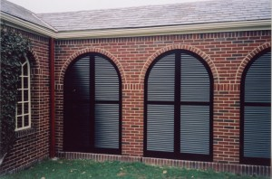 arched shutters block the wind in this breezeway