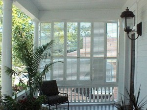 operable louvered shutters act as a windbreak on this second story porch